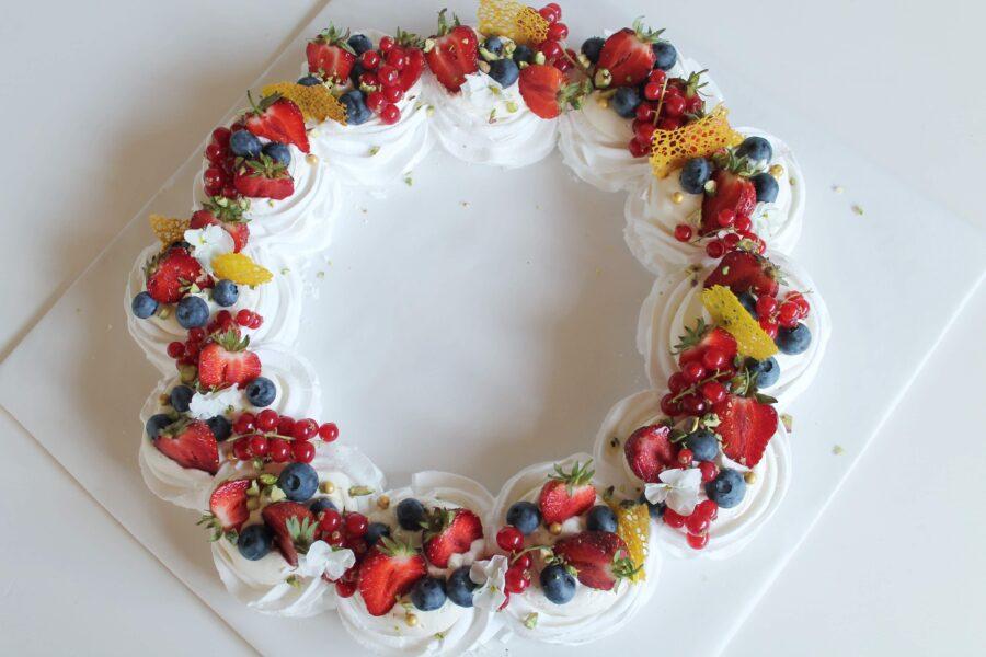 Opskrift på sprød pavlovakrans med friske bær.